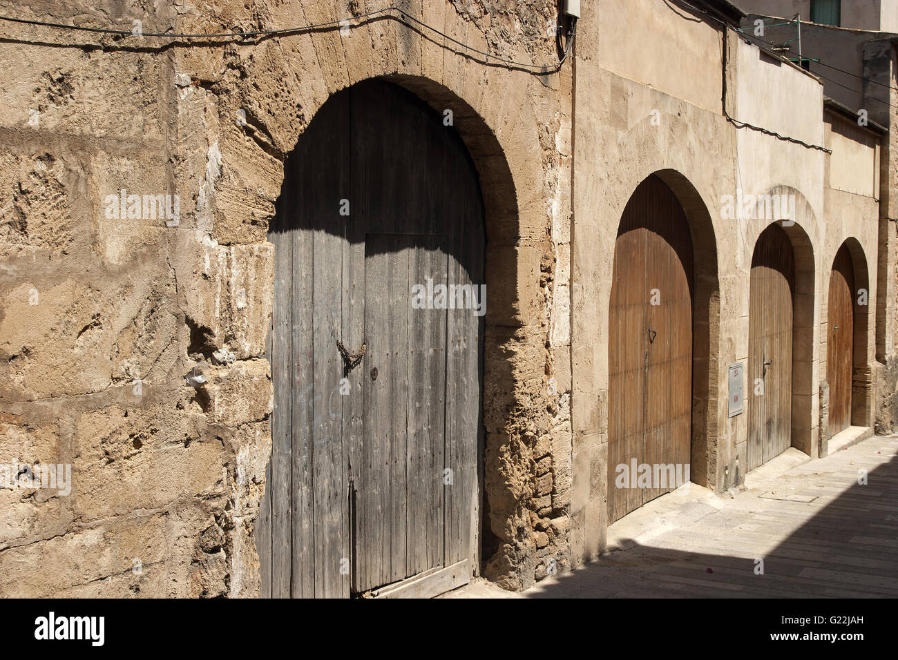 a beautiful wide angle photo of wooden old arched doors in the town of Alcudia, Palma de Mallorca, Spain, seaside, - Stock Image