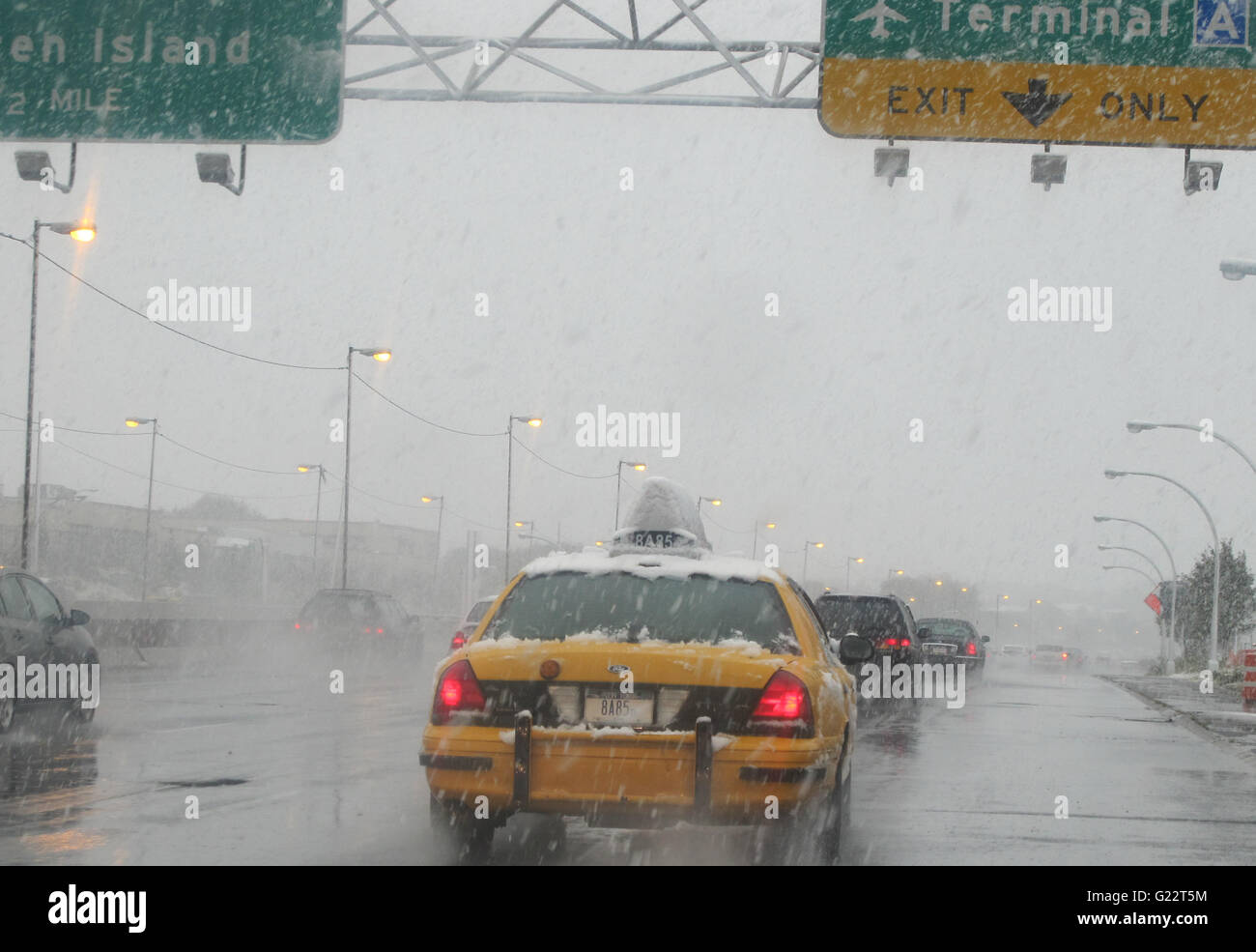 New York City yellowcab negotiates slippery conditions during snow storm on Grand Central Parkway - Stock Image