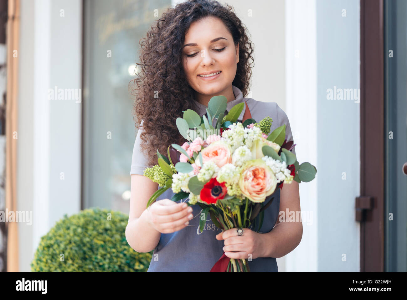 Smiling cute young woman florist with flower bouquet standing in front of shop - Stock Image