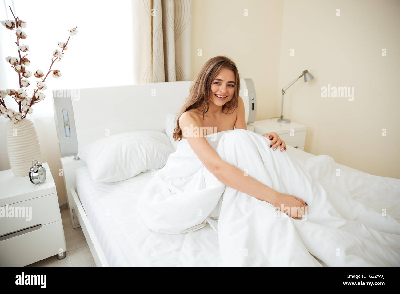 Smiling woman sitting on the bed under blanket and looking at camera at home - Stock Image