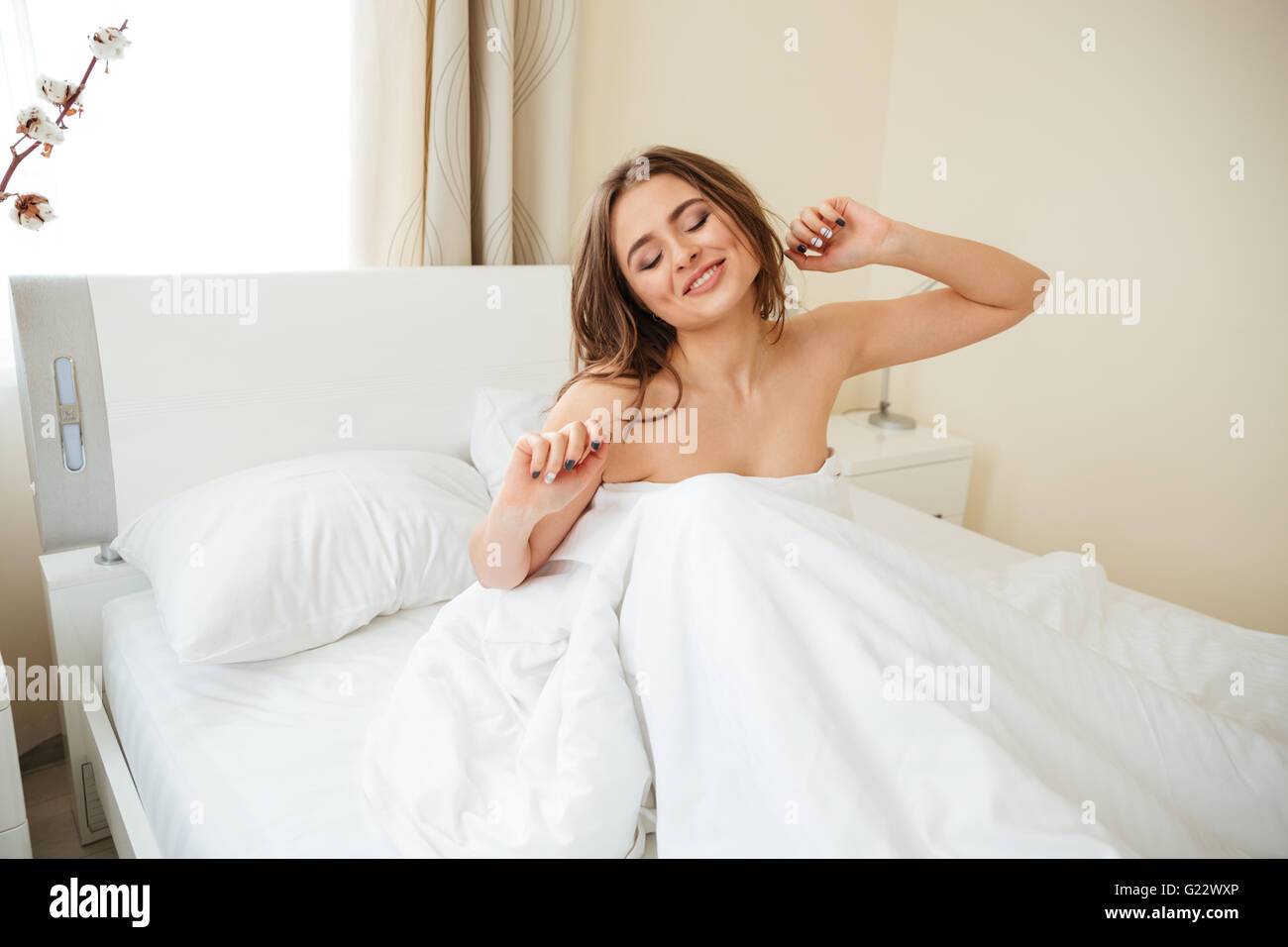 Happy woman stretching hands in the bed at home - Stock Image