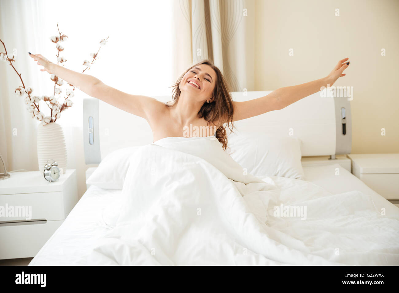 Happy woman stretching hands on the bed at home - Stock Image