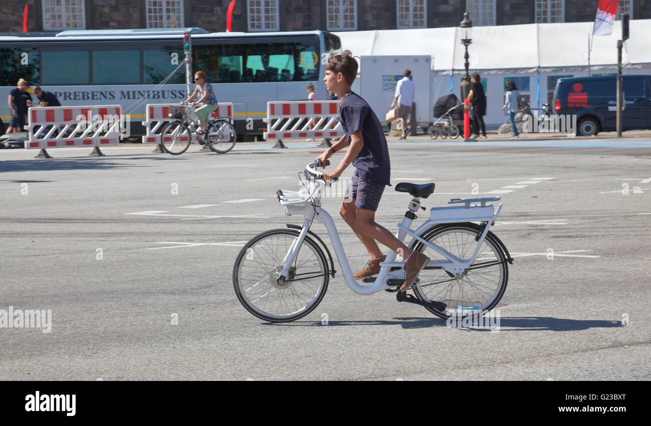 A visiting boy in a speedy start on a Gobike electric motor assisted city bike in the Copenhagen streets at Christiansborg. - Stock Image
