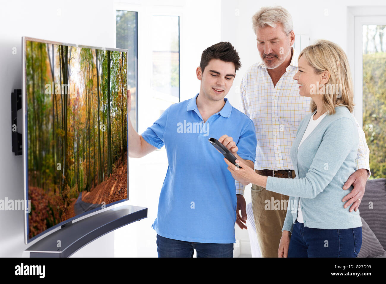 Man Demonstrating New Television To Mature Couple At Home - Stock Image