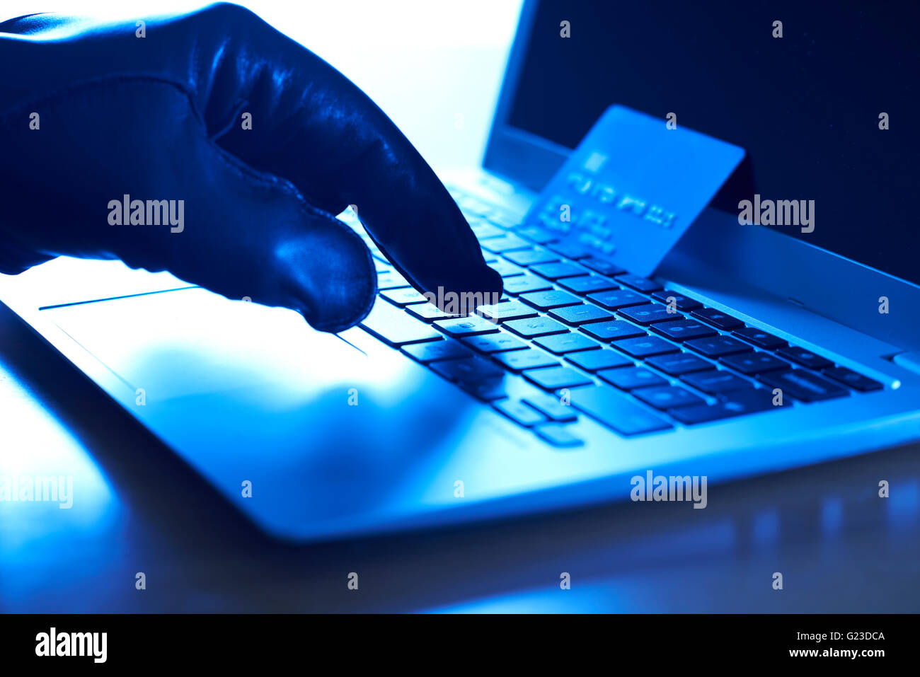 Cyber Criminal With Stolen Credit Card And Laptop - Stock Image