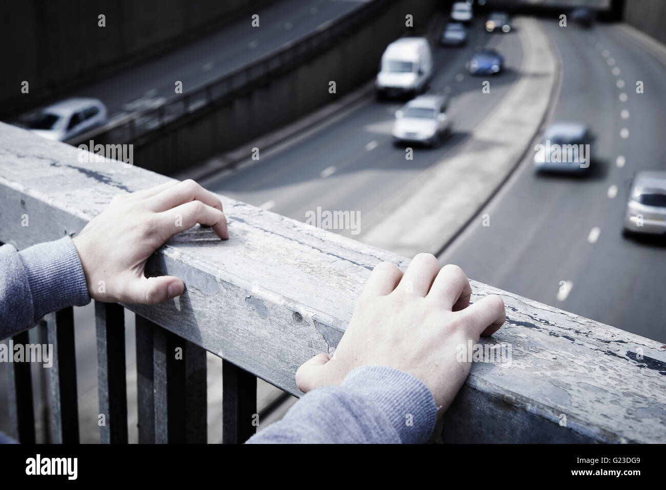 Depressed Young Man Contemplating Suicide On Road Bridge - Stock Image