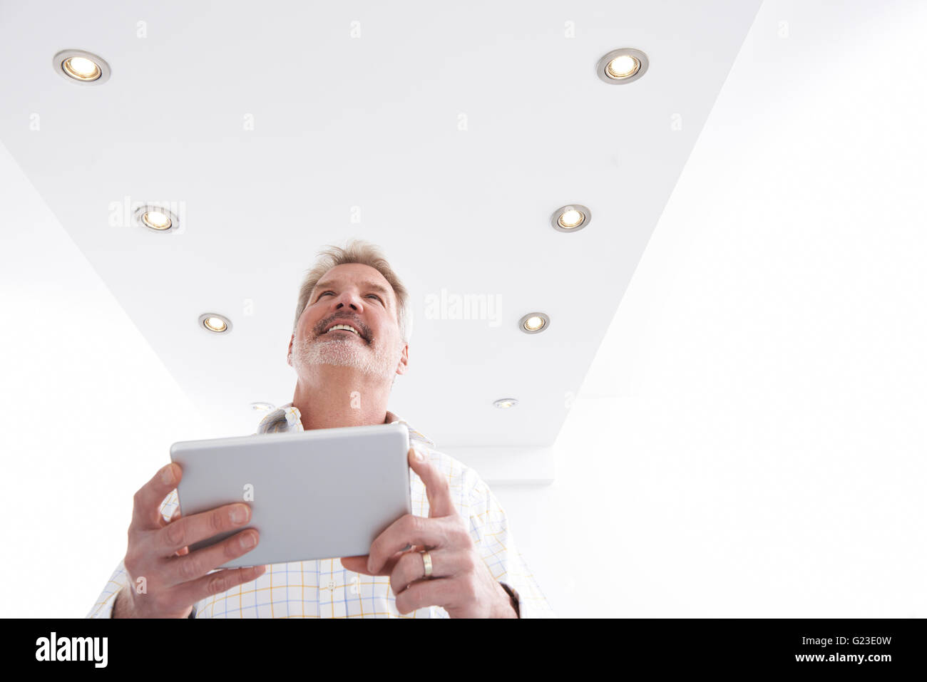 Man Controlling Lighting With App On Digital Tablet - Stock Image