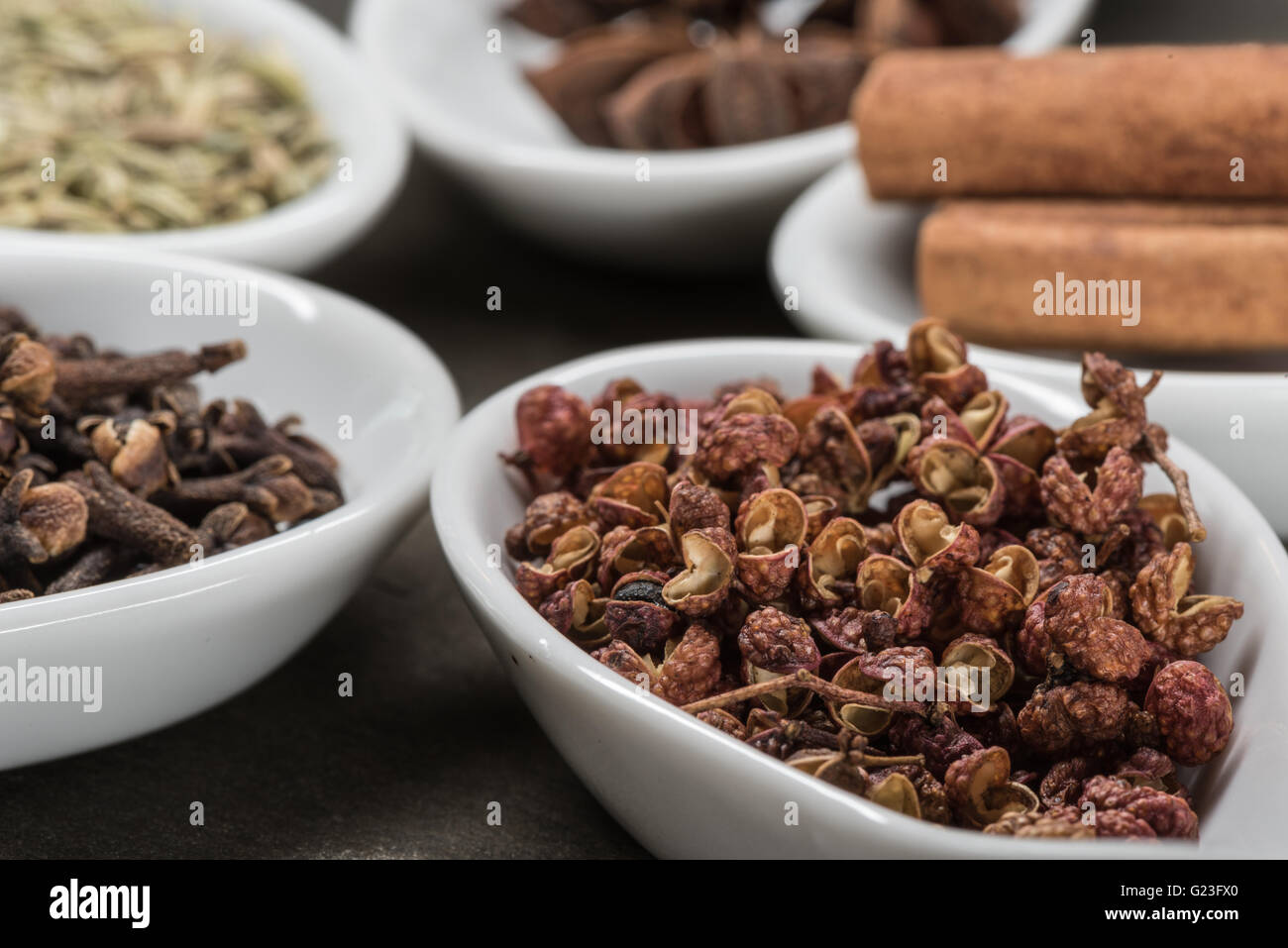Szechuan Peppercorns in White Spoon with Chinese five spices in background - Stock Image