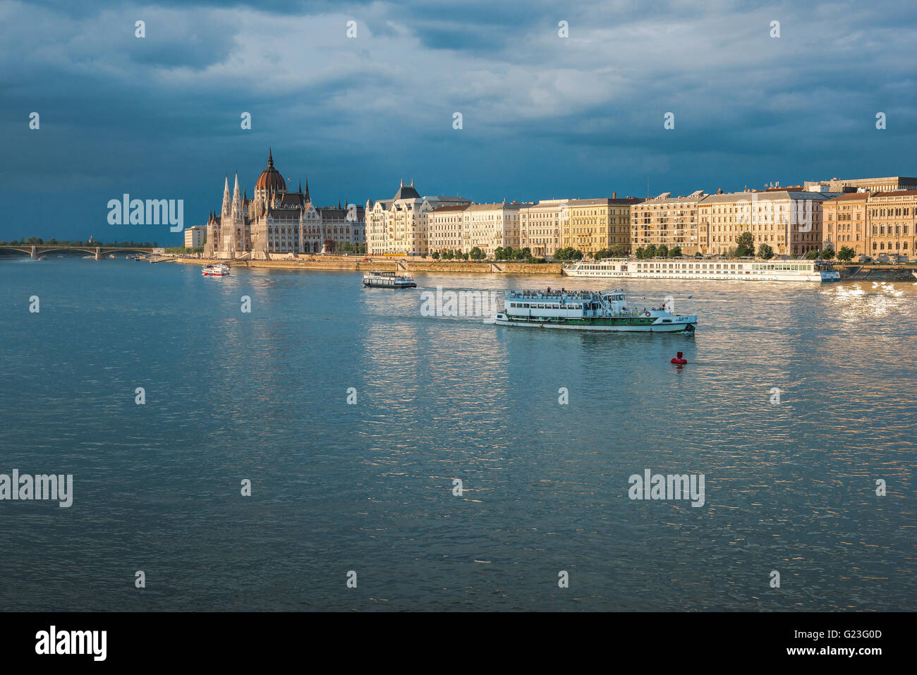 The south embankment (the Pest side) of the Danube River in Budapest illuminated at sunset, with the Hungarian Parliament - Stock Image