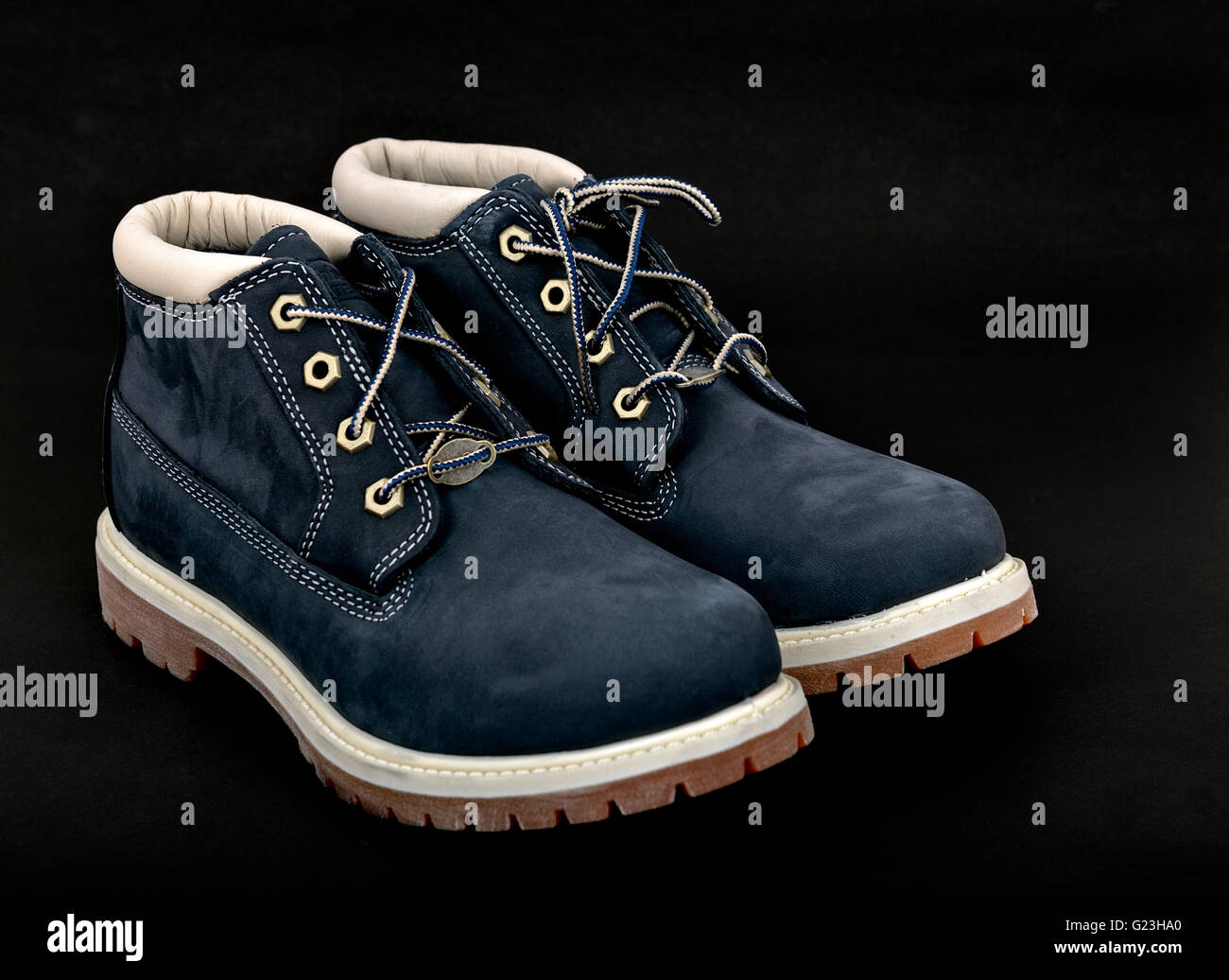 Navy lady's boots with shoelace and sole on black background. - Stock Image