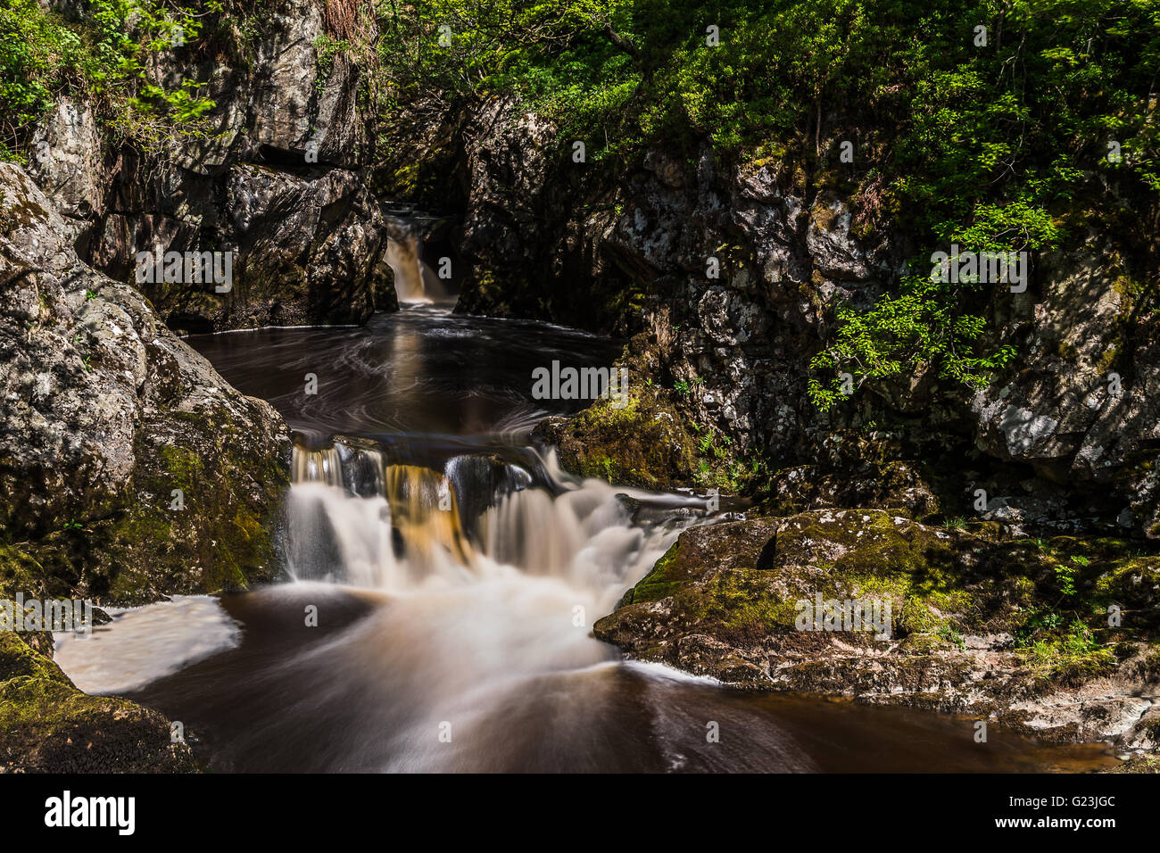 Water flows out of a circular pool at the Snowfalls cascade along the Ingleton waterfalls trail in North Yorkshire. - Stock Image