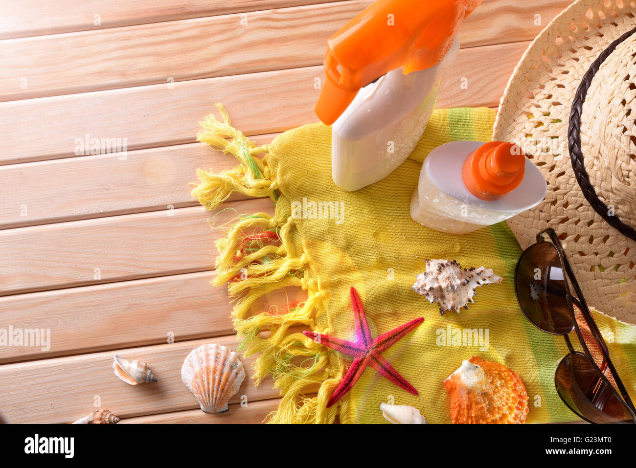 Two spray suncream on towel and wooden slats with shells. Horizontal composition. Top view - Stock Image