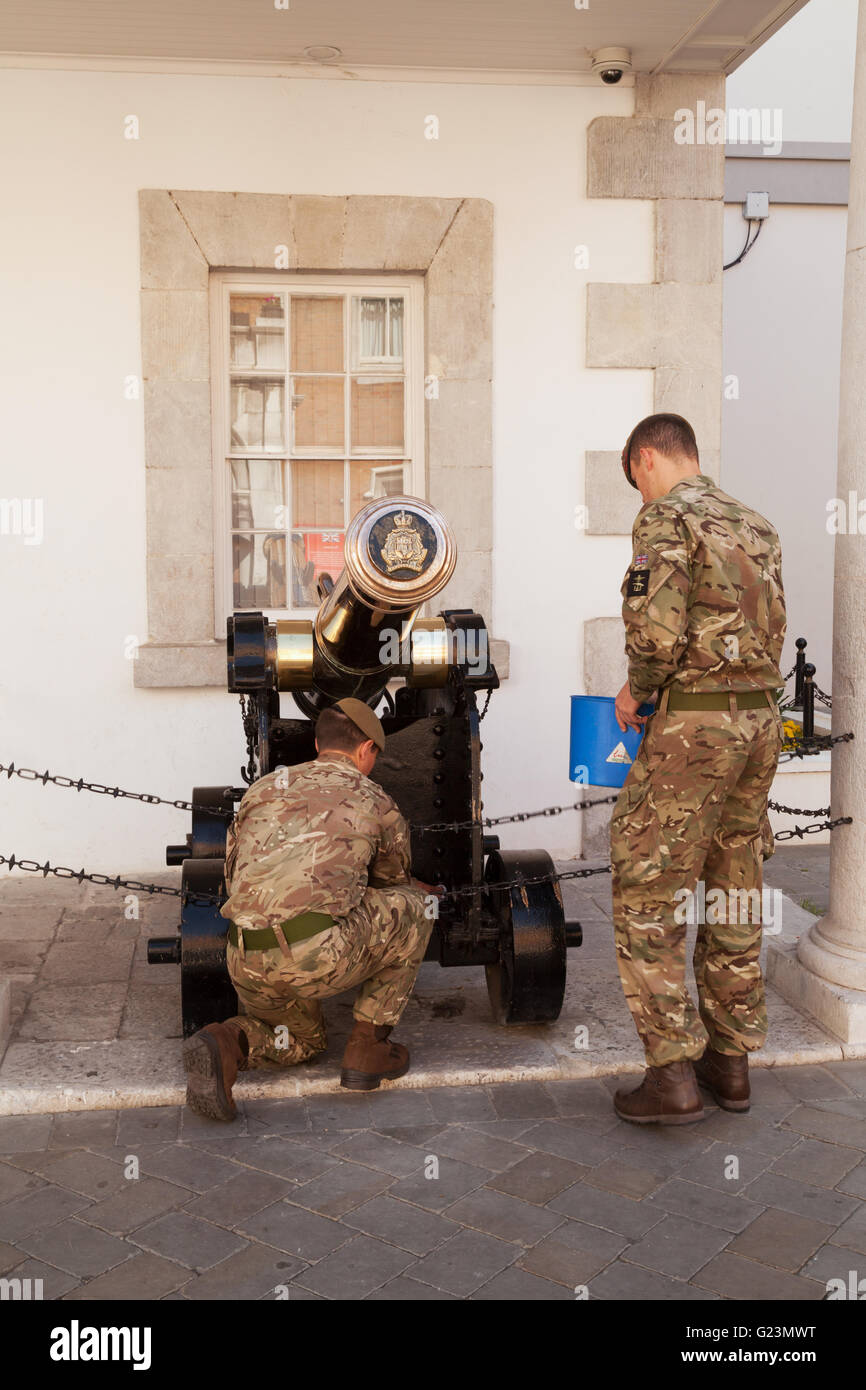 British soldiers cleaning the cannon in the Guardhouse opposite the Governors Residence ( The Convent ), Main Street - Stock Image