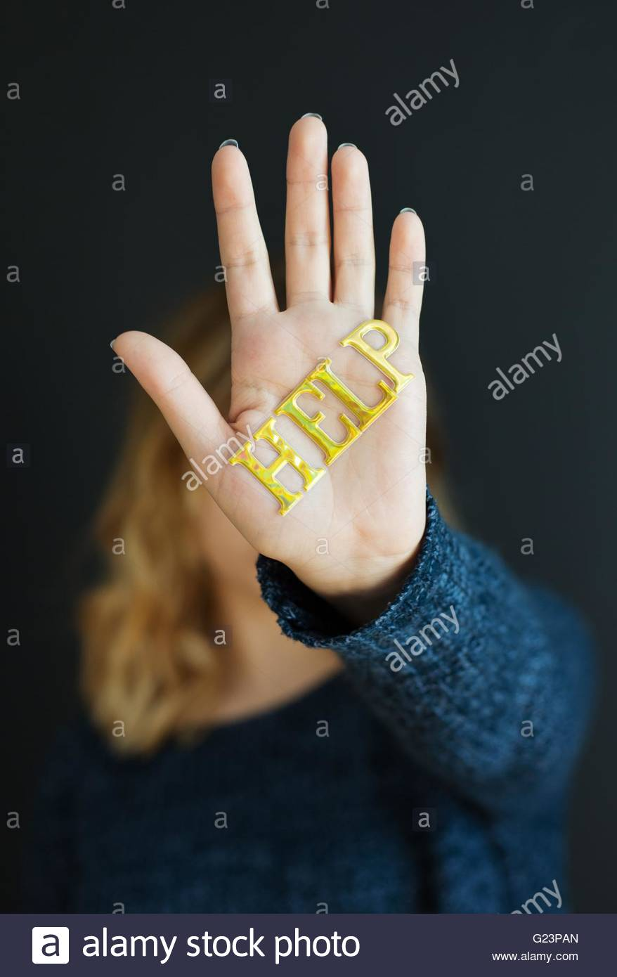 "A girl with the word ""help"" written on her hand which is shielding her face. Stock Photo"