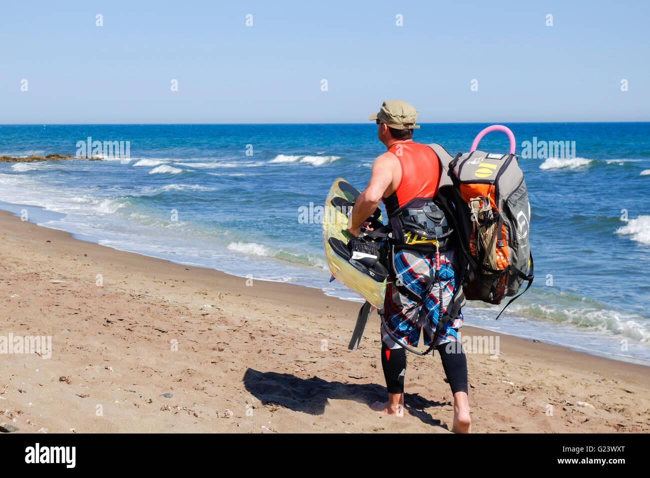 Kitesurfer carrying heavy gear at mediterranean sea kitesurfing, kitesurf,  Malaga, Spain. - Stock Image