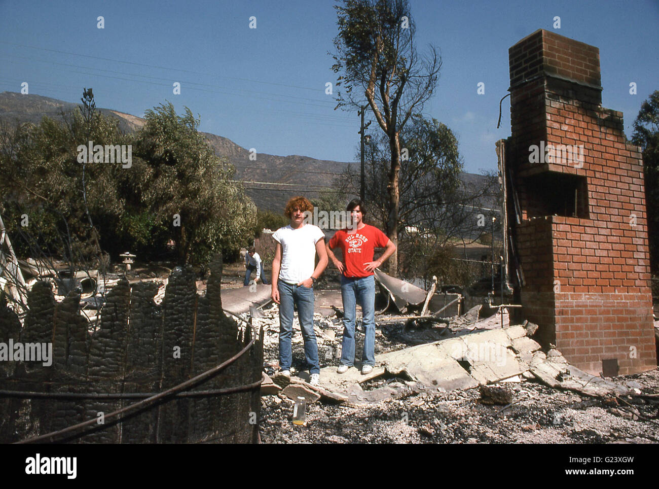 John Paul Getty III , grandson of billionnaire J Paul Getty, and friend Michael Riordan at their burned out home - Stock Image