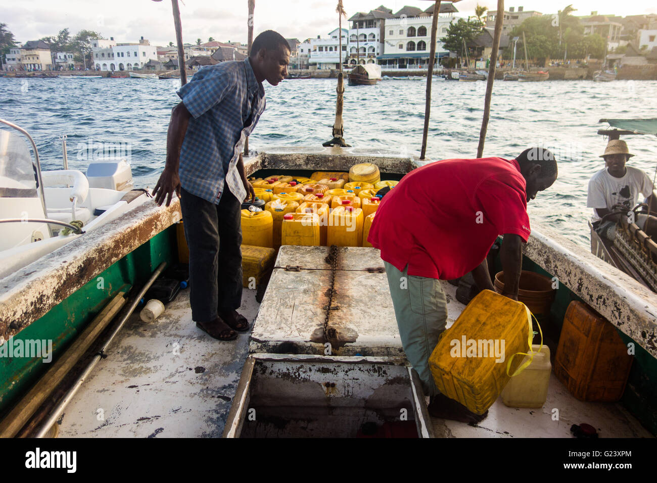 A man picks up fuel from a refueling boat in Lamu, Kenya Stock Photo