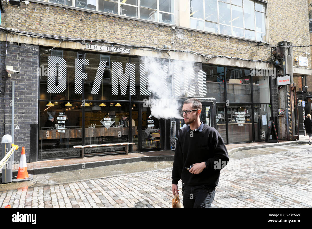 Man vaping walking by DF/Mexico Mexican restaurant on Dray Walk & Hanbury Street near Brick Lane in East London - Stock Image