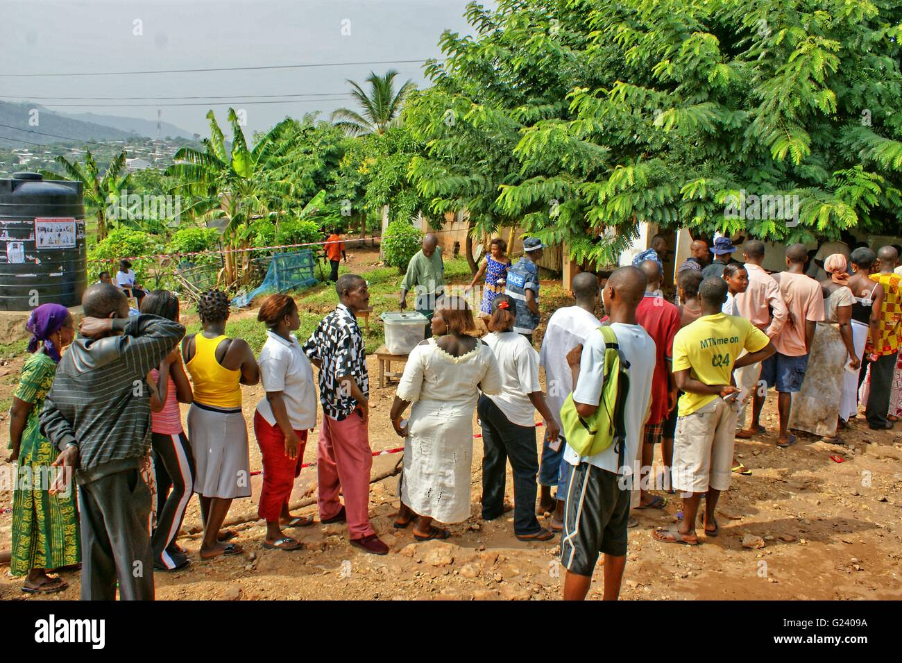 Ghana Voters waiting patiently, to vote. Man putting his vote into the sealed box. Ghana General Election. - Stock Image