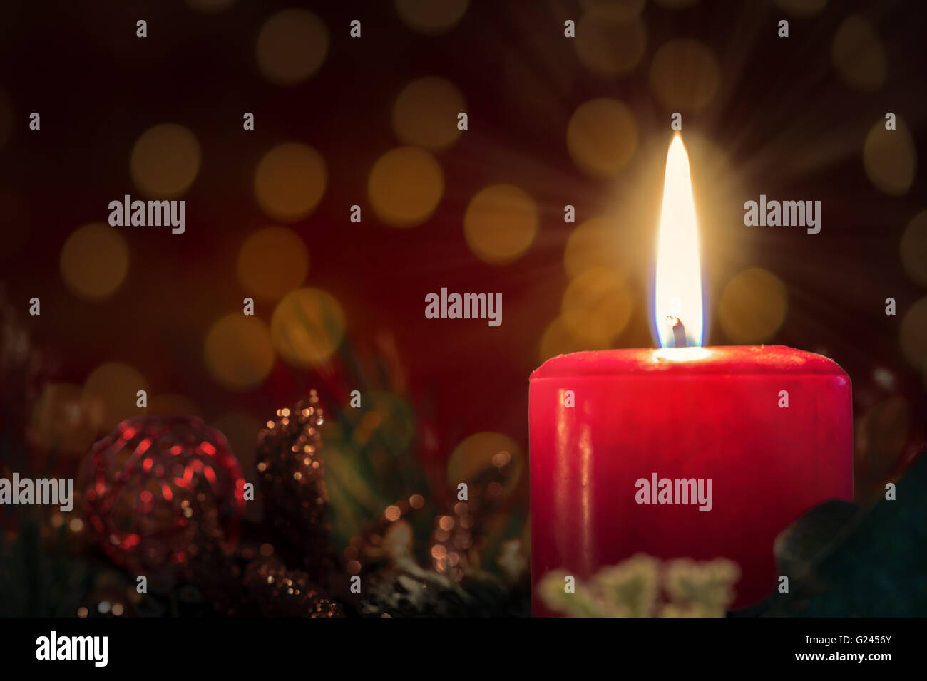 Christmas decoration with burning red candle. Blurred background and copy space. - Stock Image