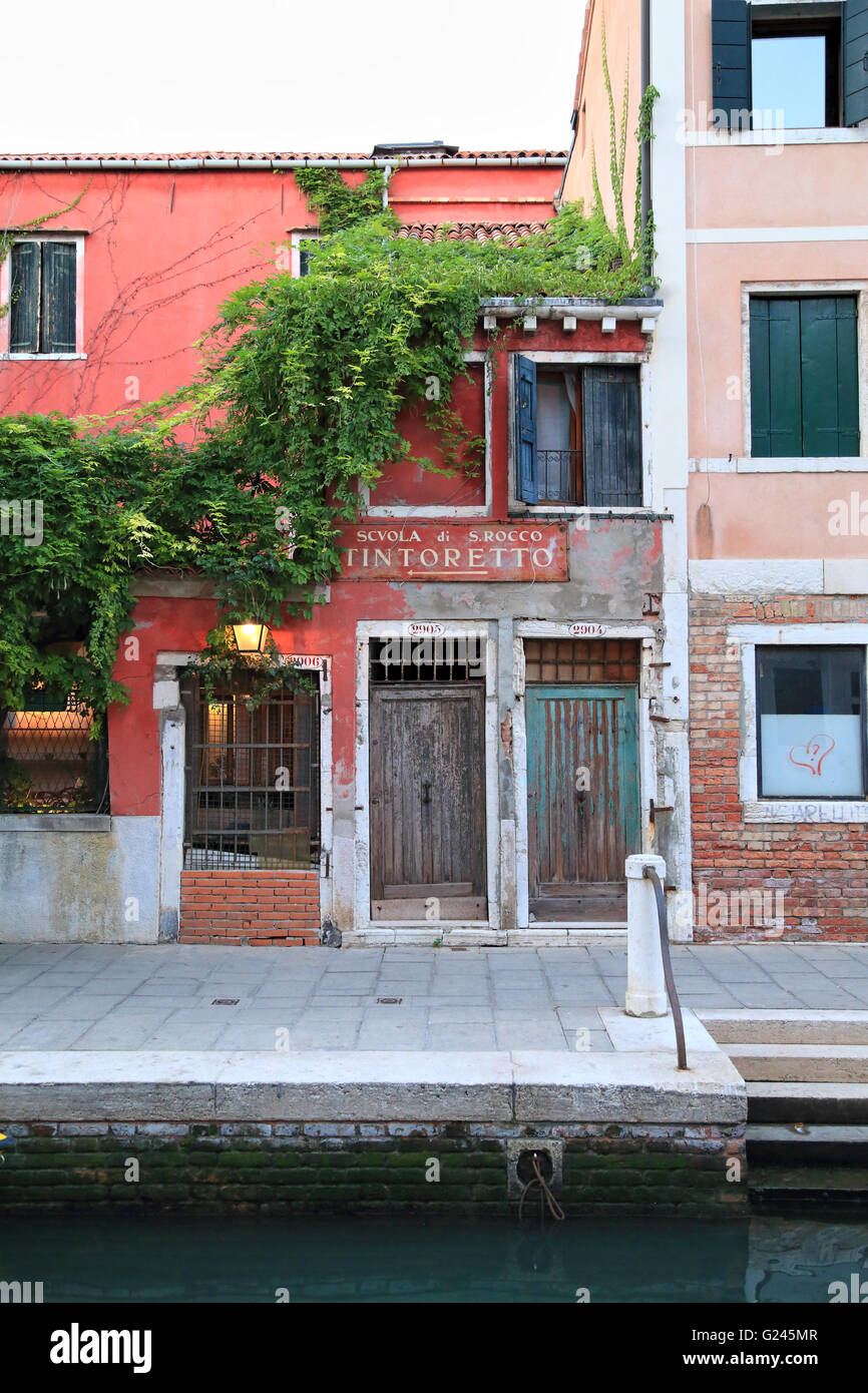 Scuola Grande di San Rocco sign at an old canal house in Venice - Stock Image