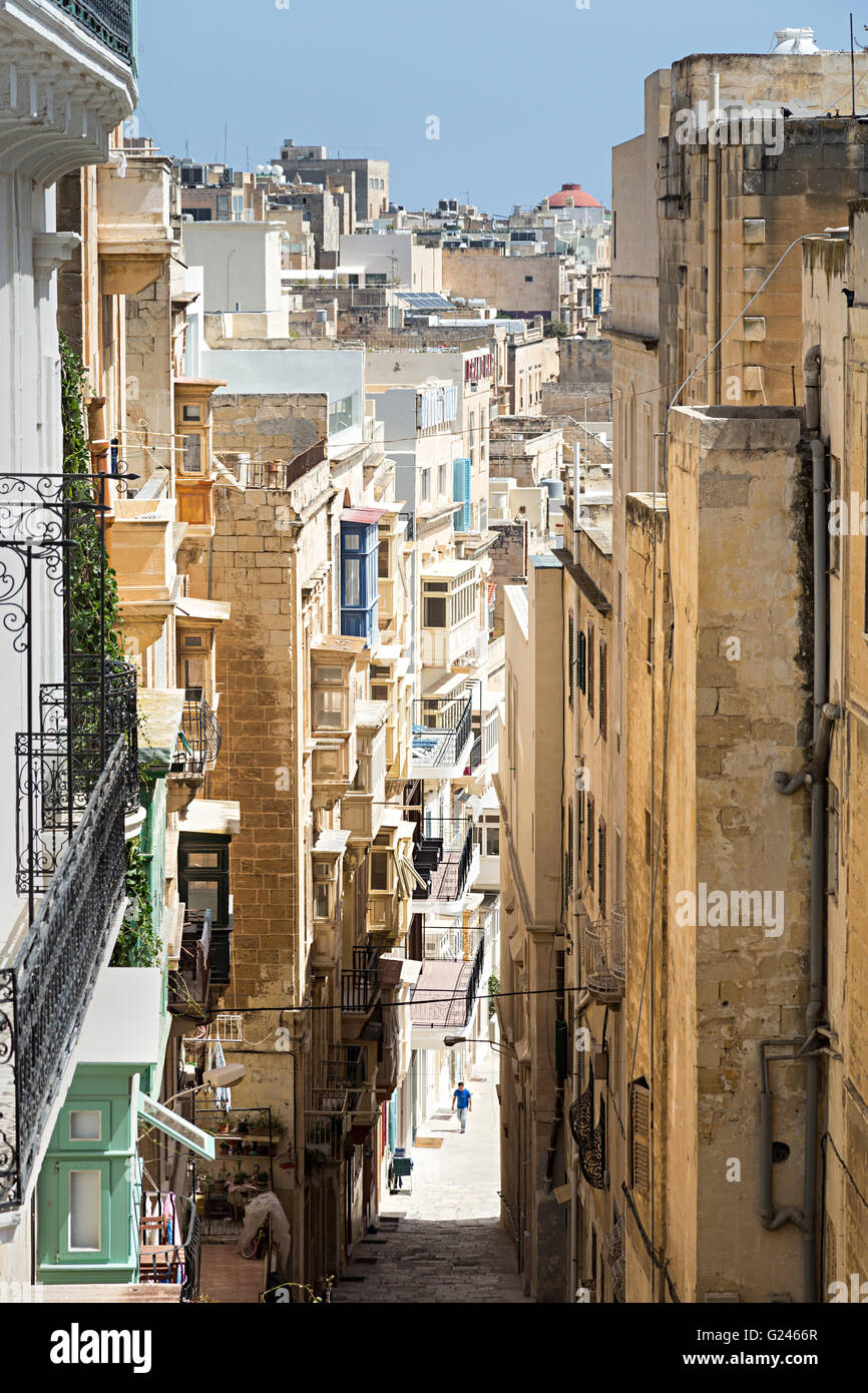 Person in narrow street with tall buildings, Valletta, Malta - Stock Image