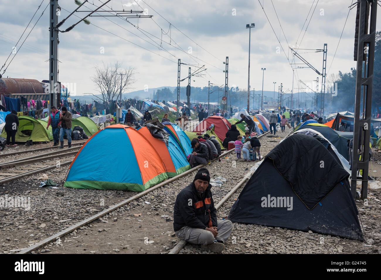 Refugees from Syria sit by their tents on March 17, 2015 in the refugee camp of Idomeni, Greece. - Stock Image