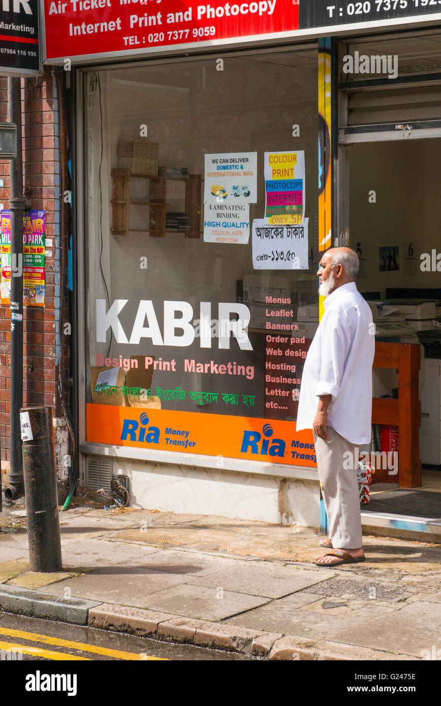 England London East End typical street scene Bangladeshi bearded man male by his print & design shop Kabir money - Stock Image