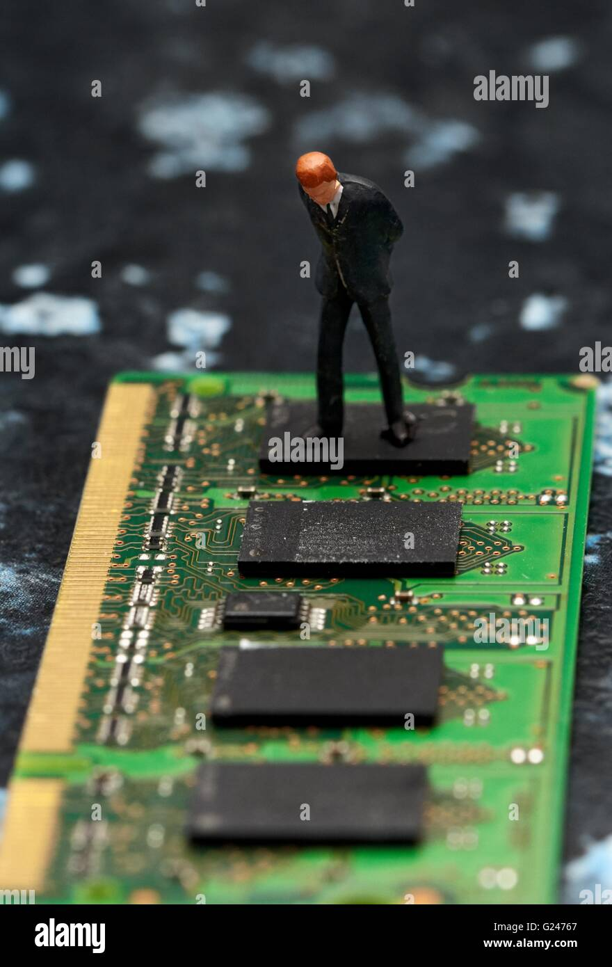 A miniature figurine businessman looking down on computer chip memory. - Stock Image