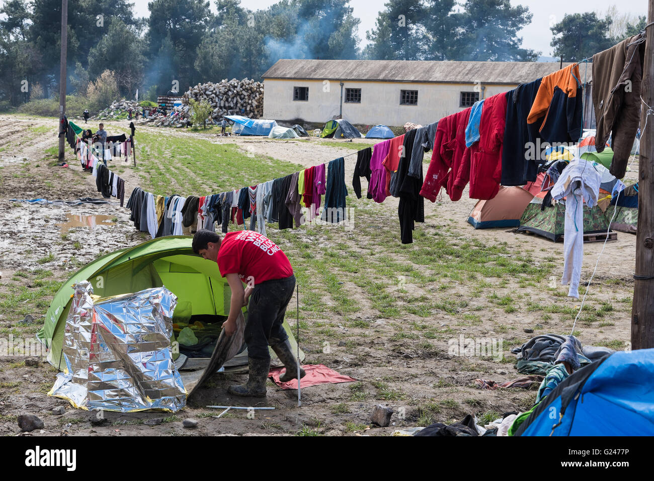 A refugee from Syria cleans his tent after heavy rain on March 17, 2015 in the refugee camp of Idomeni, Greece. - Stock Image