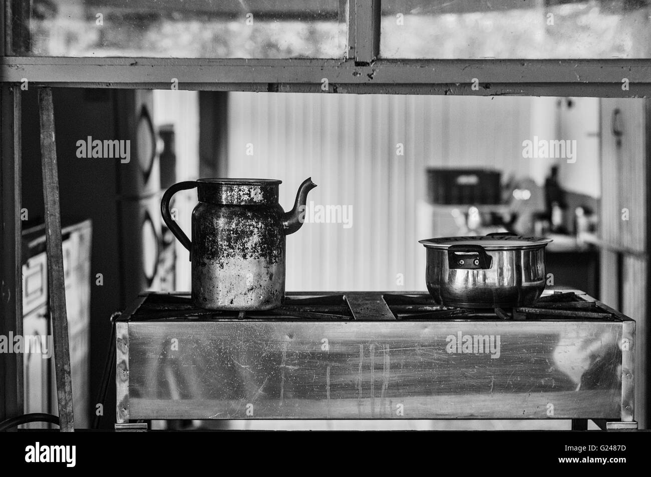 Old Kitchen with a kettle and a cooking pot on a stove viewed through a window - Stock Image