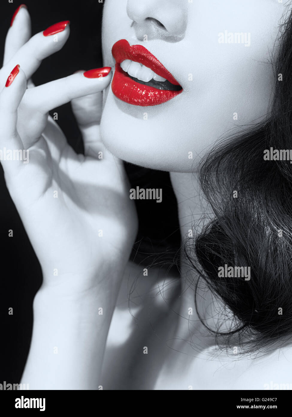 Woman's mouth with bright red lipstick and nail varnish - Stock Image
