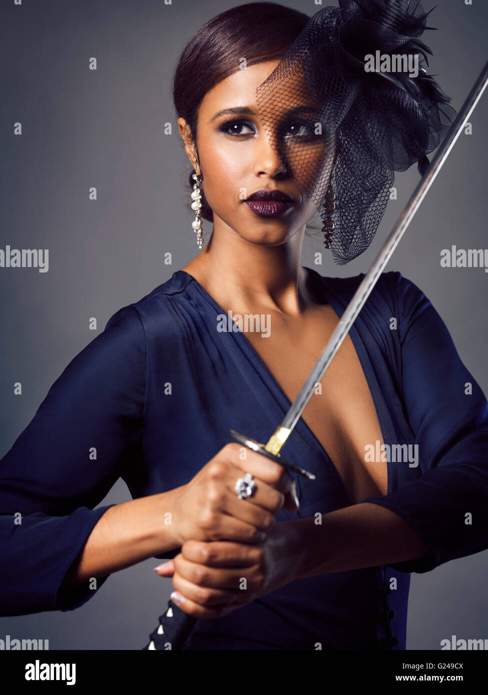 Woman with black veil holding a Katana sword in her hands Stock Photo