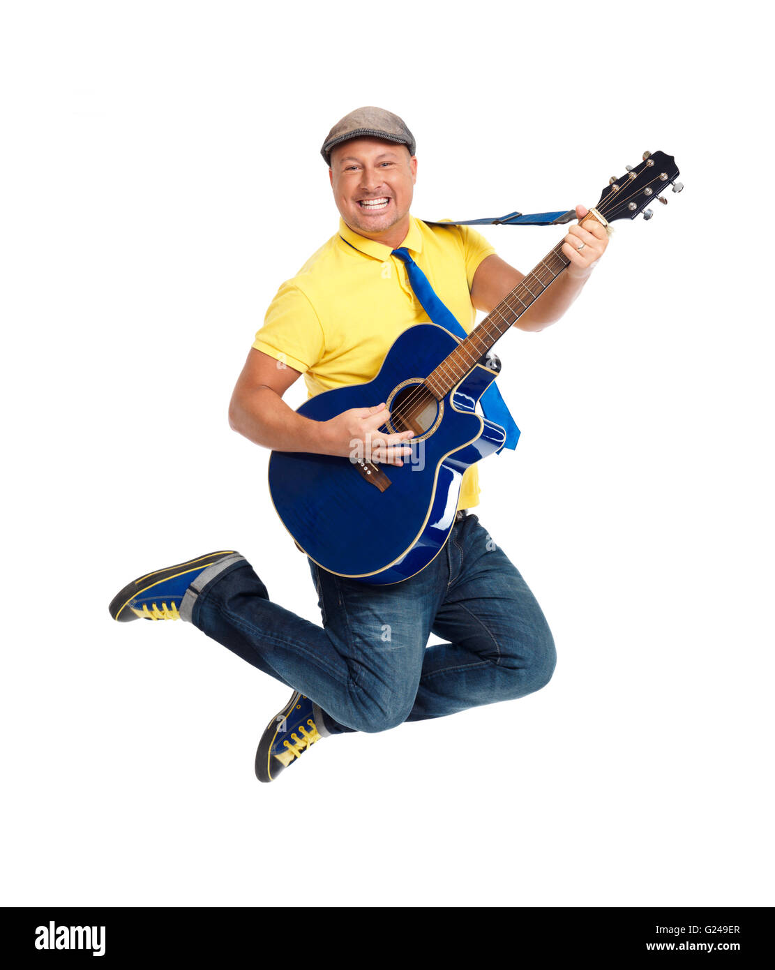 Happy smiling guitar player jumping with an acoustic guitar