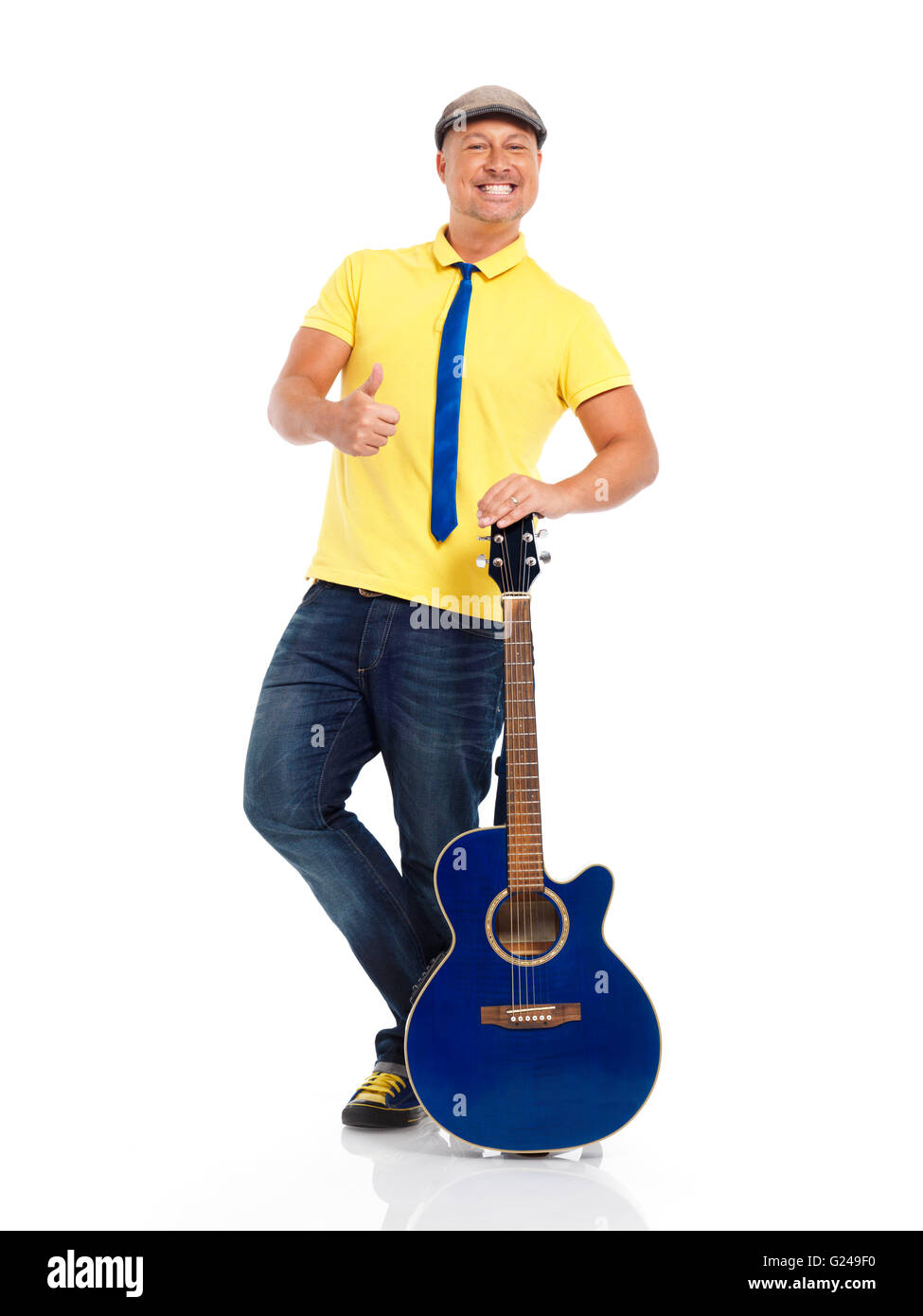 Smiling guitar player standing with an acoustic guitar - Stock Image