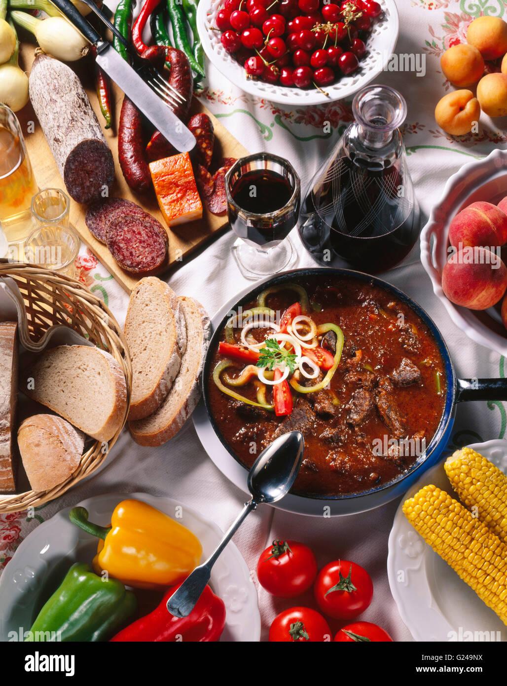 Hungarian national cuisine, salami, sausages, paprika, goulash, red wine - Stock Image