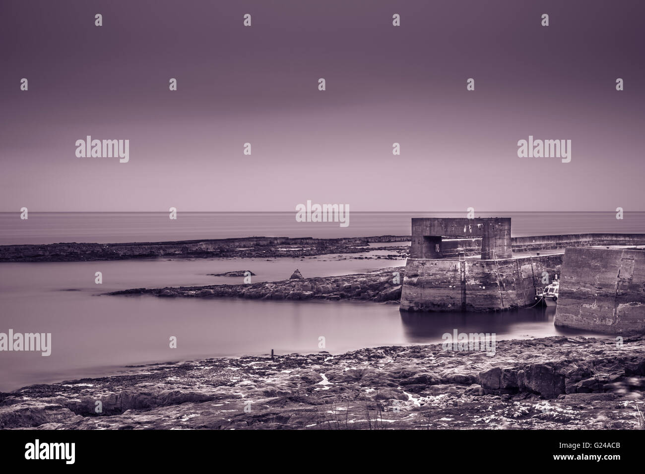Craster harbour wall and a fishing boat in Northumberland, England Stock Photo