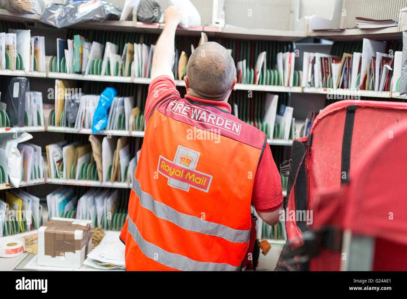 Royal Mail Sorting Office. A man works. - Stock Image