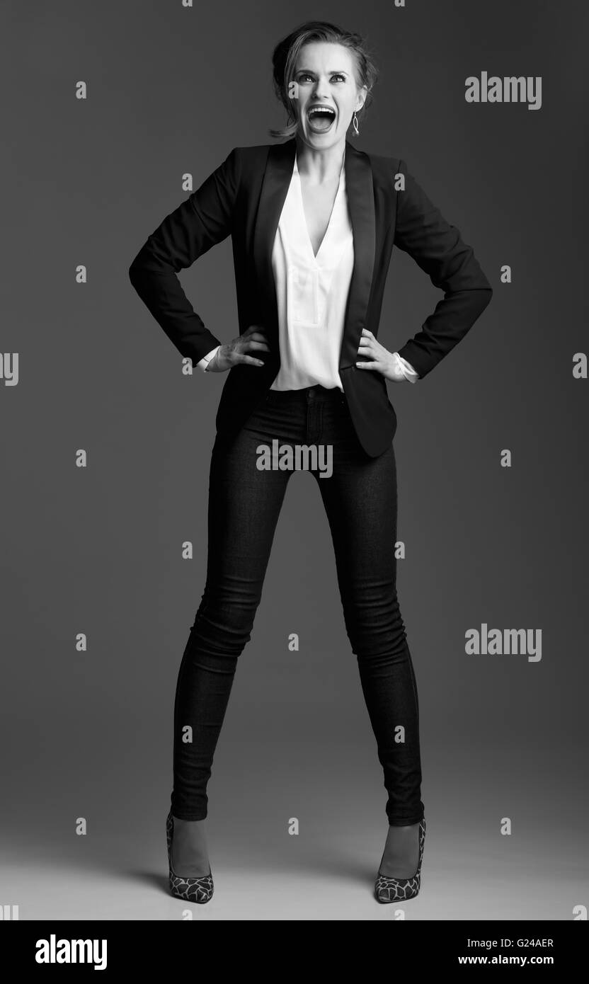Contemporary woman in black and white aesthetic. Full length portrait of excited modern elegant woman posing against - Stock Image