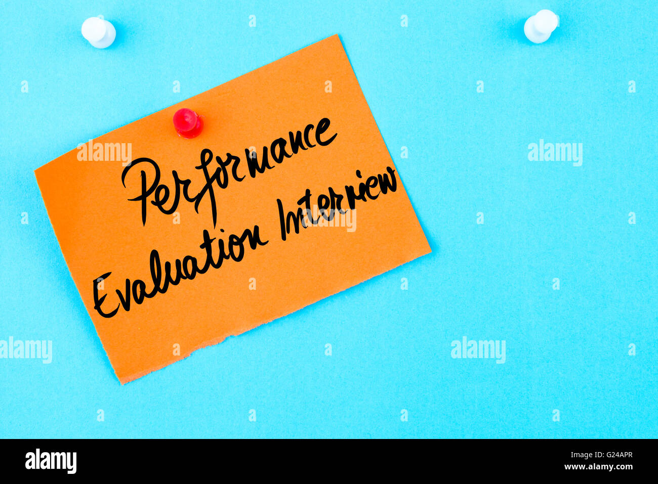 Performance Evaluation Interview written on orange paper note pinned on cork board with white thumbtack, copy space - Stock Image