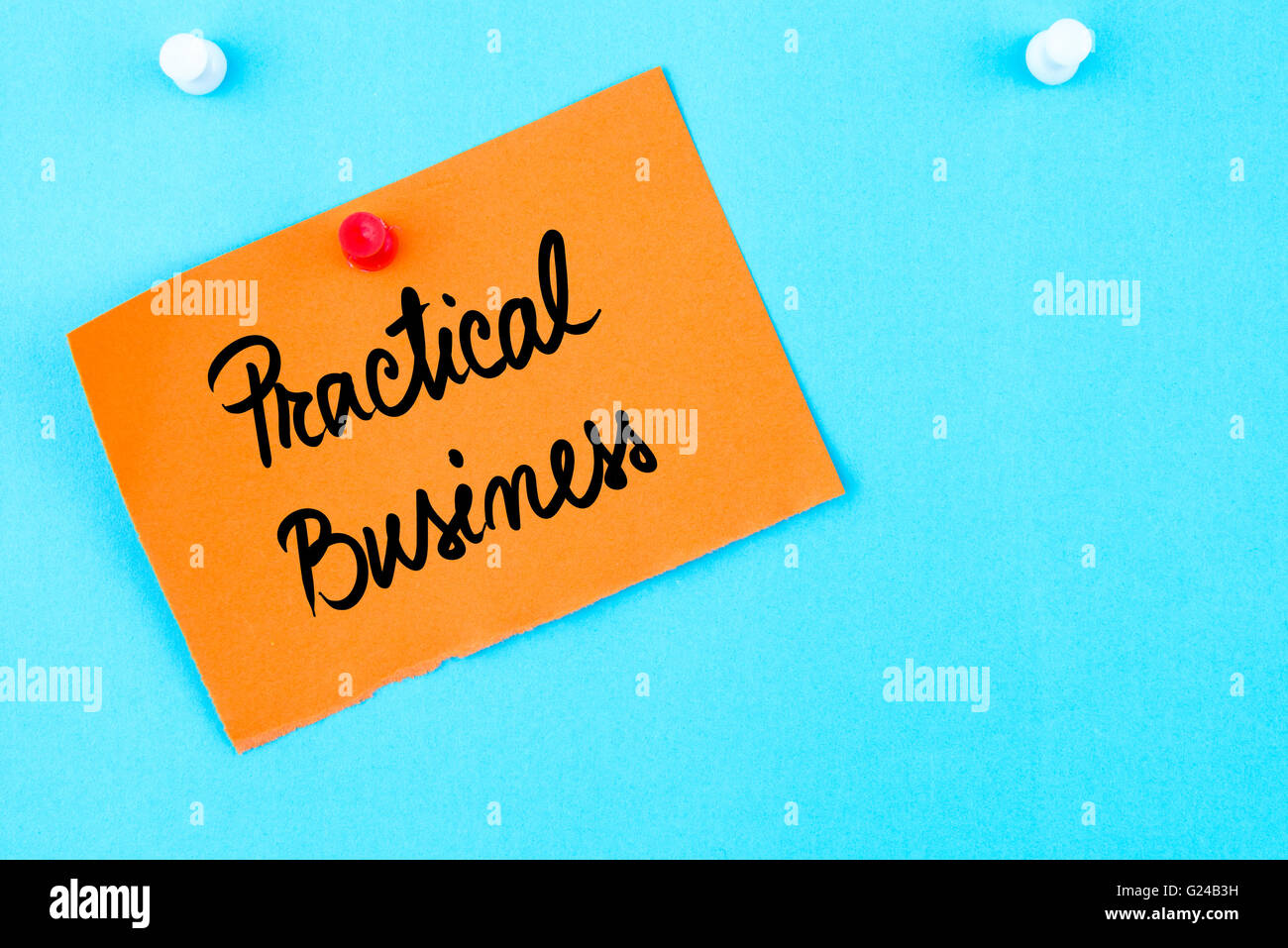 Practical Business written on orange paper note pinned on cork board with white thumbtack, copy space available - Stock Image