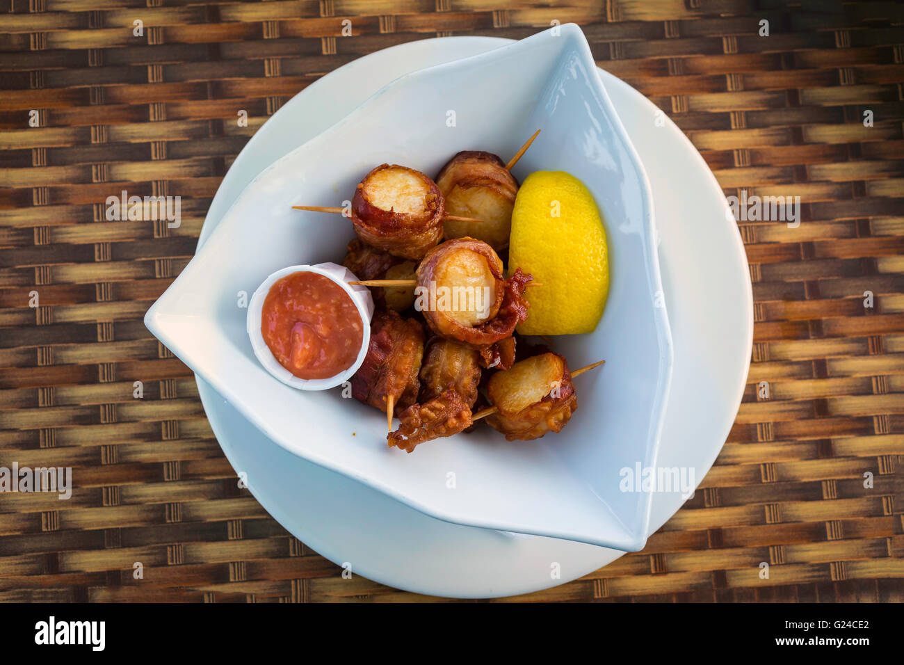 Bacon wrapped scallops with a slice of lemon and some seafood sauce in a serving dish. - Stock Image