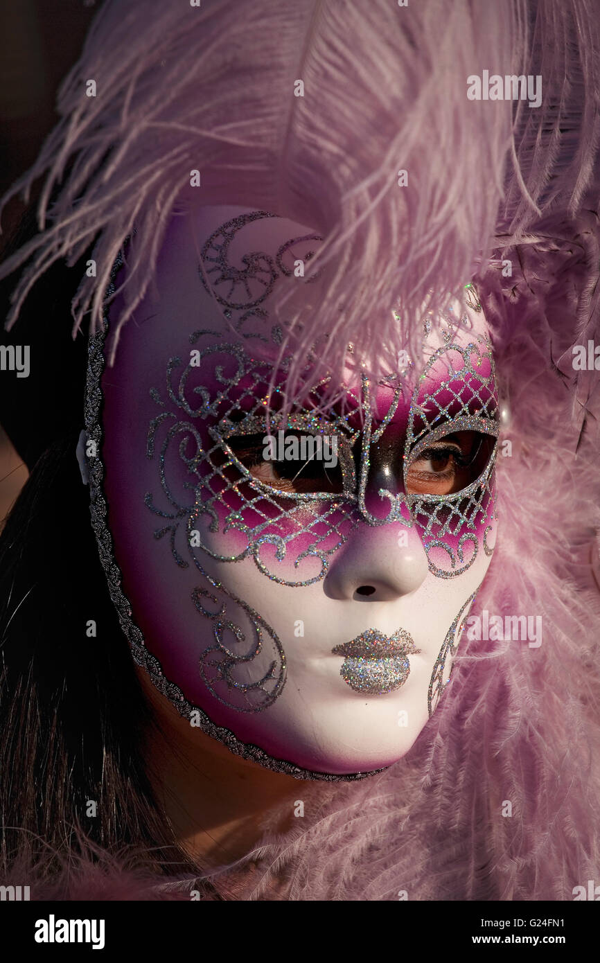 Masked carnevale reveller, Piazza San Marco, Venice, Italy: close-up of feathered mask - Stock Image