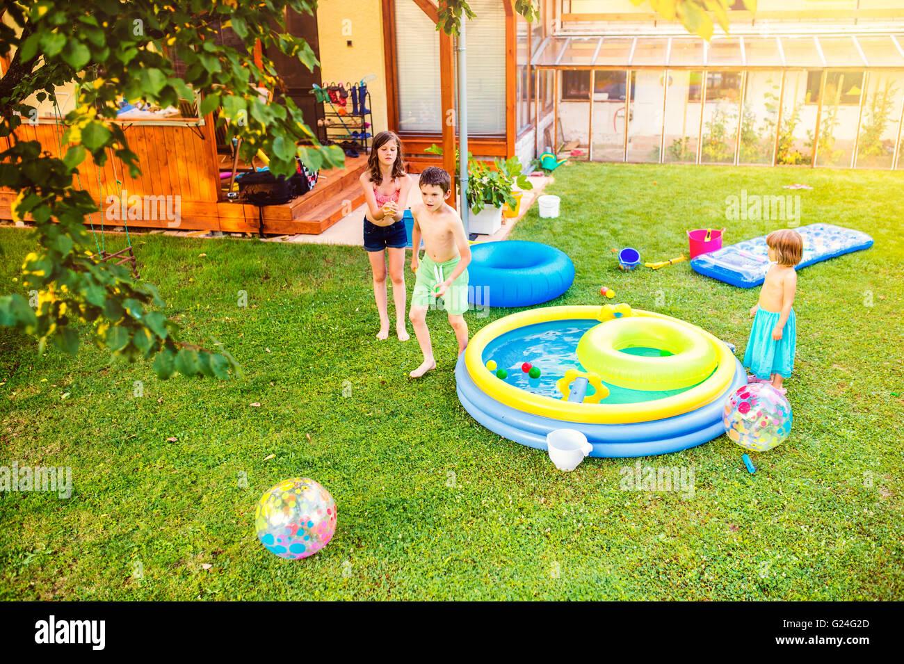 Boy splashing girls with water gun in the garden - Stock Image
