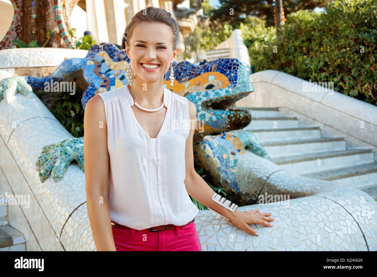 Get inspired by Park Guell in your next trip to Barcelona, Spain. Portrait of happy young woman near multicolored Stock Photo