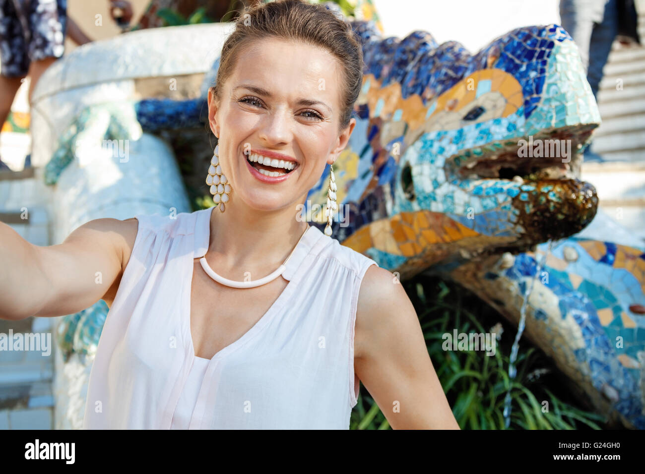 Get inspired by Park Guell in your next trip to Barcelona, Spain. Smiling young woman taking selfie near multicoloured Stock Photo