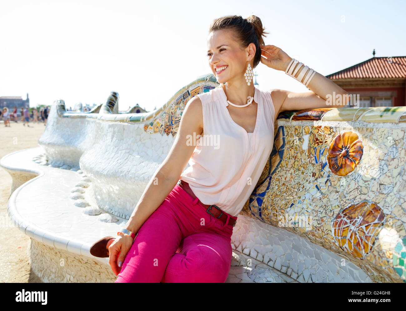 Get inspired by Park Guell in your next trip to Barcelona, Spain. Happy young woman sitting on the famous trencadis Stock Photo