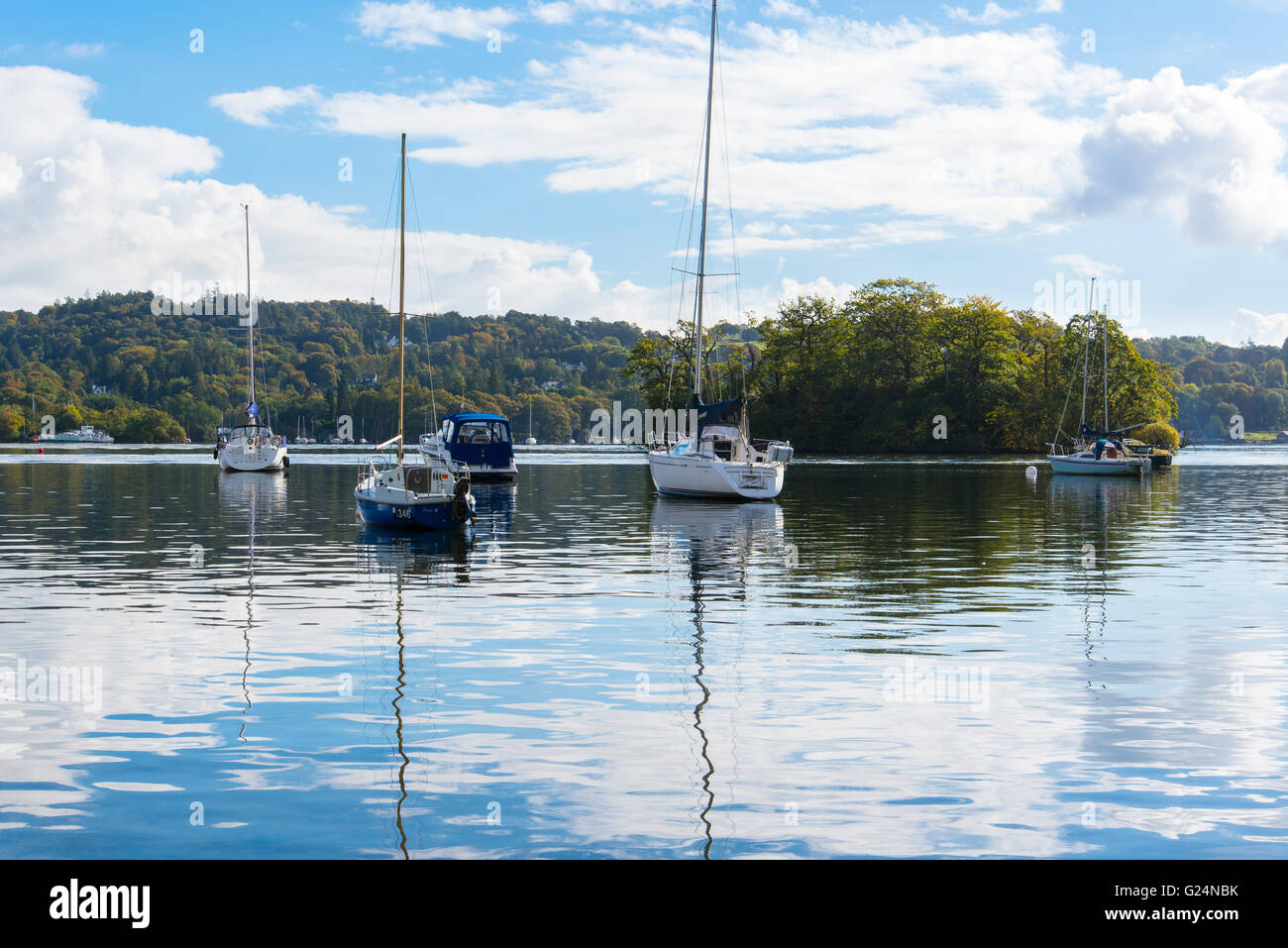 Moored yachts on Windermere in the Lake District Cumbria. The island is Crow Holme. - Stock Image