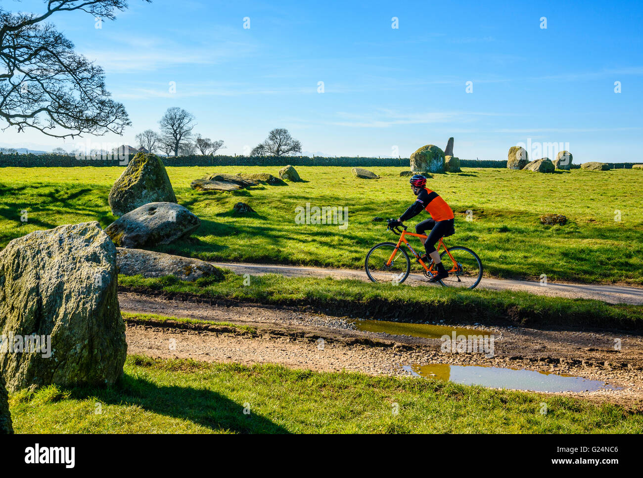 Cyclist riding through the stone circle of Long Meg and her Daughters in the Eden Valley Cumbria - Stock Image