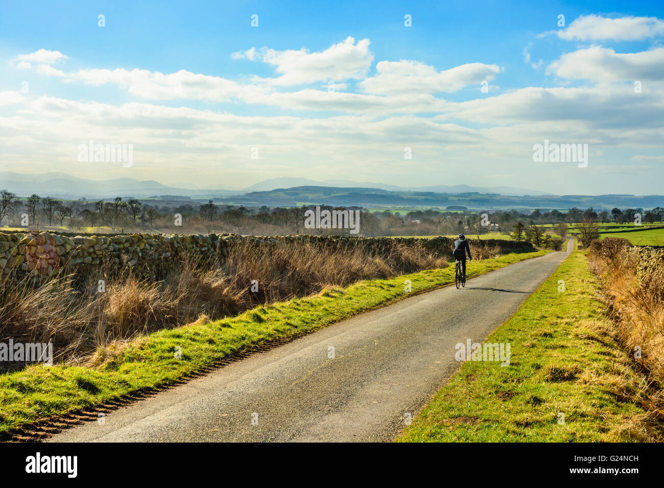 Cyclist on lonely road between Kirkland and Skirwith in the Eden Valley Cumbria with the Lakeland Fells in the distance - Stock Image
